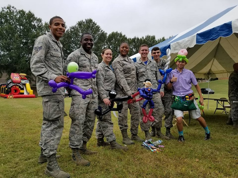Reserve Citizen Airmen pose for a photo with their balloon animals at this year's Family Day Oct. 14, 2017 at Dobbins Air Reserve Base, Ga. Family Day is held here annually as a way of bringing families on base to see what their Reserve Citizen Airmen do on drill weekends. (U.S. Air Force photo/Senior Airman Lauren Douglas)