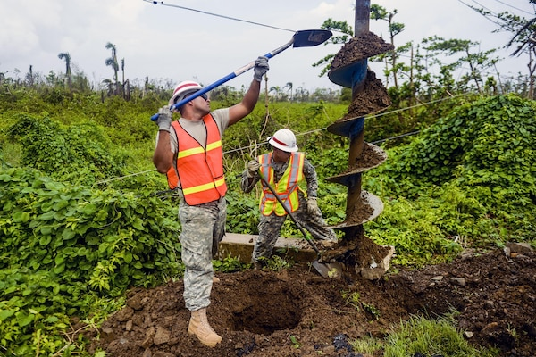Army Sgts. Luis Ruiz, left, and Jonathan Quinonez clean the dirt off an auger as they dig a hole to place a concrete power pole in Rio Grande, Puerto Rico, Oct. 19, 2017, while supporting Hurricane Maria relief efforts. Air Force photo by Master Sgt. Joshua L. DeMotts