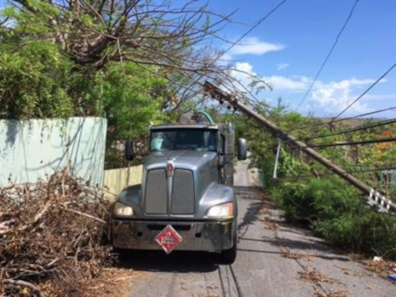 A fuel truck contracted by the Defense Logistics Agency makes its way through fallen electrical poles and downed trees in Puerto Rico.