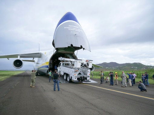 Members of the 821st Contingency Response Group help to offload line trucks from a Ukrainian Anatov 124-100m cargo transporter onto the tarmac of Jose Aponte De La Toore Airport in Ceiba, Puerto Rico, Oct. 11, 2017. The line trucks will be used to help repair the electrical grid in Puerto Rico that was destroyed after Hurricane Maria devastated the island.