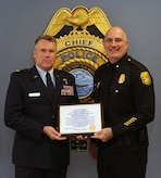 Maj. Robert Simmons (left), a reserve Medical Service Corps officer with the 45th Aeromedical Evacuation Squadron, MacDill Air Force Base, Fla., received a Citizen Appreciation Award on Oct. 19, 2017 from the Tampa Police Department Interim Chief Brian Dugan (right) for his response to a traffic accident and his subsequent life-saving actions. In July 2017, having just finished his monthly reserve training and leaving the base, Simmons witnessed a car accident that left one driver severely wounded as a result of an impaled object. Simmons was able to quickly secure the scene and administer life-saving care to the driver. (U.S. Air Force photo by Tech. Sgt. Peter Dean)