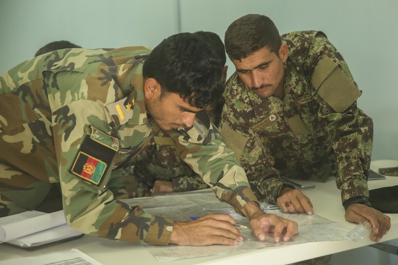 Afghan National Army soldiers with Artillery Brigade, 215th Corps plot grids during a map reading class as part of an artillery course at Camp Shorabak, Afghanistan, Oct. 21, 2017. More than 20 soldiers with the brigade, including forward observers, artillery crewmen and a fire direction control team are undergoing the eight-week course, which teaches proper employment of the 122mm howitzer D-30. (U.S. Marine Corps photo by Sgt. Lucas Hopkins)