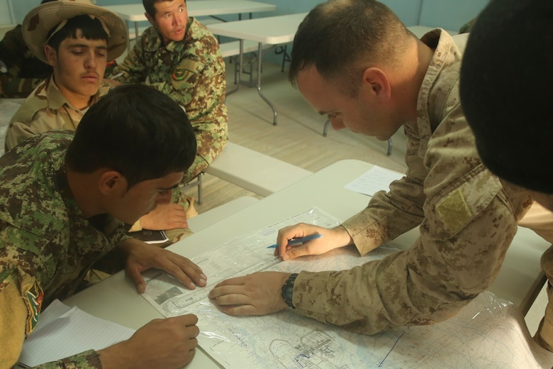 A U.S. Marine advisor with Task Force Southwest instructs Afghan National Army soldiers with Artillery Brigade, 215th Corps on proper map reading techniques during an artillery course at Camp Shorabak, Afghanistan, Oct. 21, 2017. The eight-week training program incorporates forward observers, artillery crewmen and a fire direction control team, and is designed to enhance their employment of artillery assets and gain hands-on skills with the 122mm howitzer D-30. (U.S. Marine Corps photo by Sgt. Lucas Hopkins)