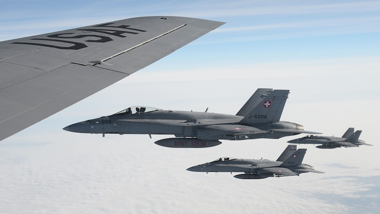Three Swiss air force F-18 Hornets fly alongside a U.S. Air Force KC-135 Stratotanker, assigned to the 100th Air Refueling Wing RAF Mildenhall, England, after aerial refueling, Oct. 20, 2017. Four F-18s received fuel during a training mission over Germany. (U.S. Air Force photo by Senior Airman Justine Rho)