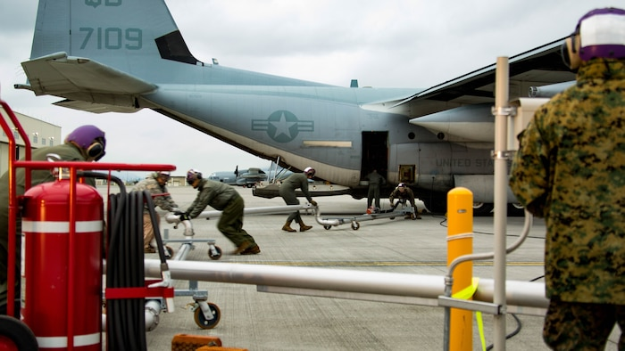 U.S. Marines and Master Labor Contractors with the Logistics Department Fuels Division fold in the Aircraft Direct Fueling System
