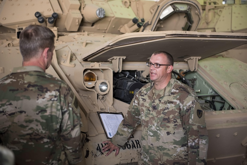 Two soldiers speaking in front of an Army vehicle