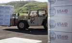 Forklift driver transports boxes in Dominica.
