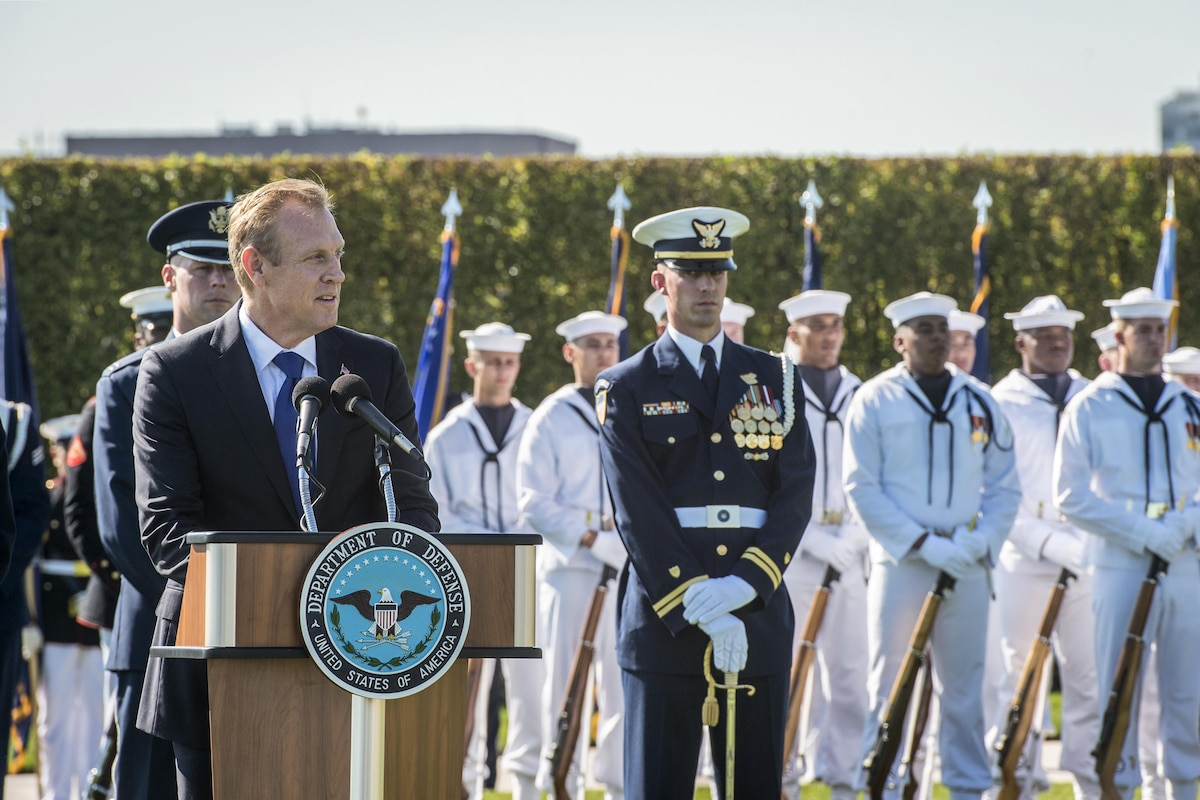 The deputy defense secretary speaks during a ceremony with sailors behind him.