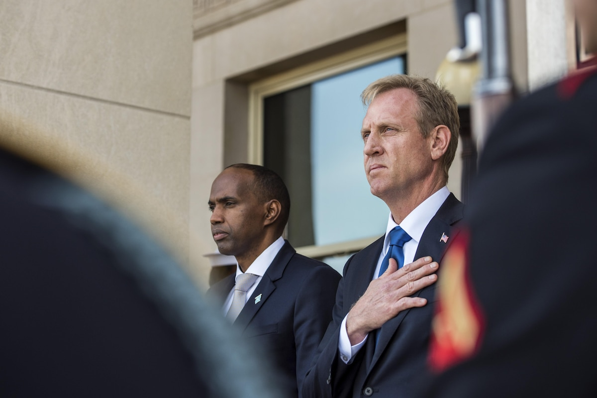 The deputy defense secretary stands with his hand over his heart during a ceremony.