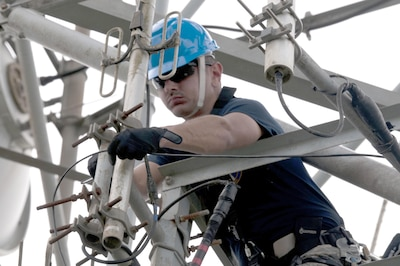 An airman works on wires up in a tower.
