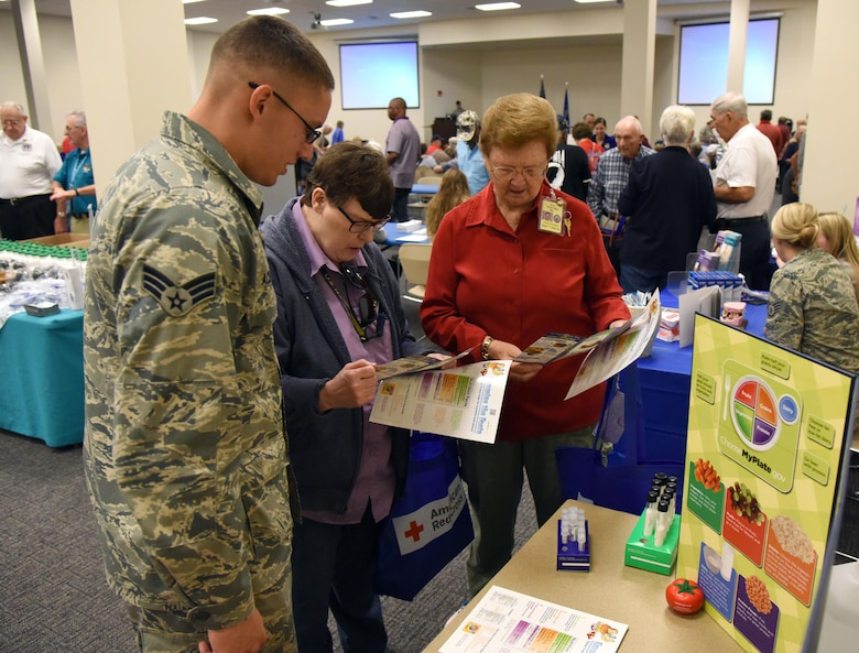 Senior Airman Juan Acevedo, 81st Diagnostic and Therapeutics Squadron diet therapy technician, provides informational pamphlets to U.S. Navy retired Senior Chief Petty Officer Faye Jefferson and U.S. Marine retired Sgt. Maj. Doris Denton during Retiree Appreciation Day at the Roberts Consolidated Aircraft Maintenance Facility Oct. 20, 2017, on Keesler Air Force Base, Mississippi. The annual event, sponsored by the Keesler Retiree Activities Office, included more than 20 displays with information pertinent to retirees and a free lunch. (U.S. Air Force photo by Kemberly Groue)