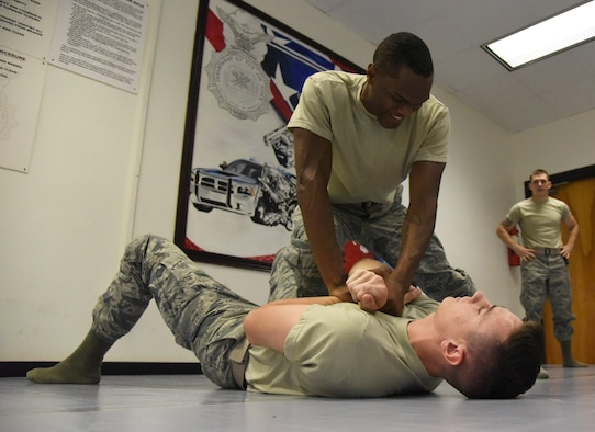 Senior Airman Curtis King II, 81st Security Forces Squadron entry controller, and Airman 1st Class Charles Wynne, 81st SFS entry controller, practice a combative technique during an 81st SFS combative training course at the SFS building Oct. 19, 2017, on Keesler Air Force Base, Mississippi. Approximately 15-20 defenders were taught skills vital to surviving a hand-to-hand ground fight using mixed martial arts and Jiu Jitsu techniques as another tool to survive a confrontational environment. (U.S. Air Force photo by Kemberly Groue)