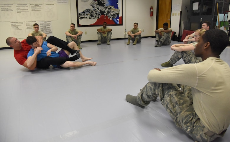 Officer Justin Depew, 81st Security Forces Squadron unit trainer, and Staff Sgt. Clarence Rainey, 81st SFS base defense operations center controller, demonstrate a combative technique during an 81st SFS combative training course at the SFS building Oct. 19, 2017, on Keesler Air Force Base, Mississippi. Approximately 15-20 defenders were taught skills vital to surviving a hand-to-hand ground fight using mixed martial arts and Jiu Jitsu techniques as another tool to survive a confrontational environment. (U.S. Air Force photo by Kemberly Groue)