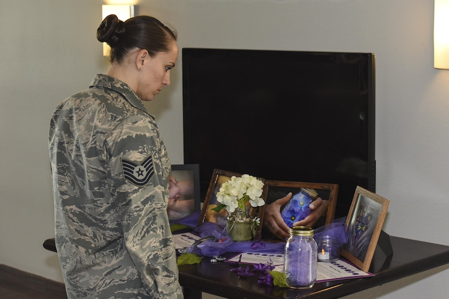 Tech. Sgt. Stephanie Godsey, 315th Training Squadron instructor, looks at a display during the Domestic Violence Awareness Month proclamation signing at the Event Center on Goodfellow Air Force Base, Texas, Oct. 20, 2017.  Each table had displays sharing stories of survivors of domestic abuse. (U.S. Air Force photo by Airman 1st Class Zachary Chapman/Released)