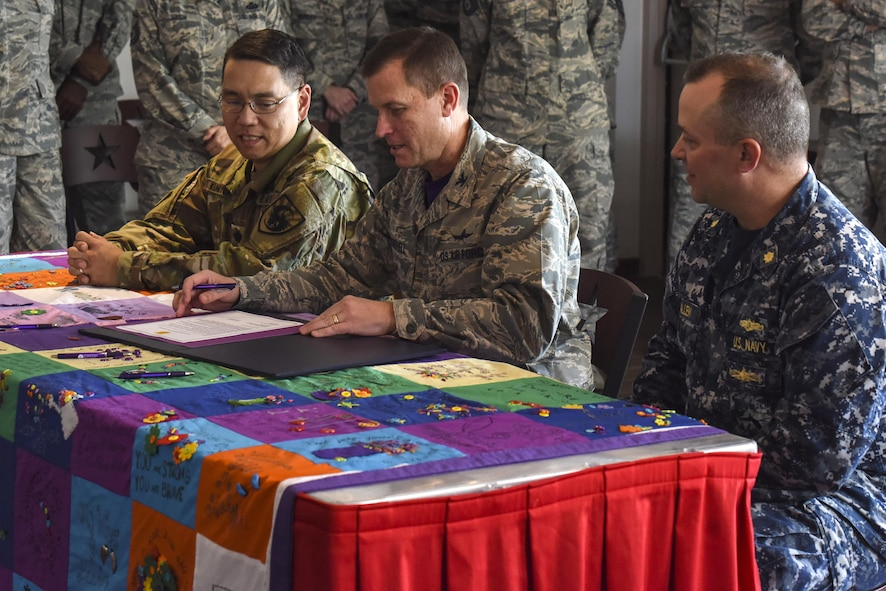 Lt. Col. Yukio Kuniyuki, 344th Military Intelligence Battalion commander, Col. Jeffrey Sorrell, 17th Training Wing vice commander, and Lt. Cmdr. Christopher Allen, Center for Information Warfare Training Detachment Goodfellow officer in charge, sign the Domestic Violence Awareness Month proclamation at the Event Center on Goodfellow Air Force Base, Texas, Oct. 20, 2017. The signing of the proclamation showed the joint forces stance against abuse. (U.S. Air Force photo by Airman 1st Class Zachary Chapman/Released)