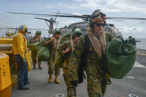 Marines assigned to Marine Heavy Helicopter Squadron 361 come aboard the amphibious assault ship USS Essex.