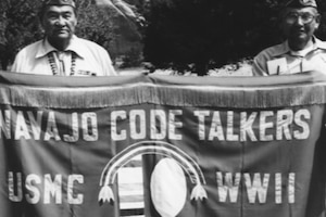 Two people hold up a banner that reads: Navajo Code Talkers USMC WWII