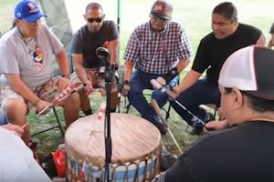 A group of people in a circle bang a drum.