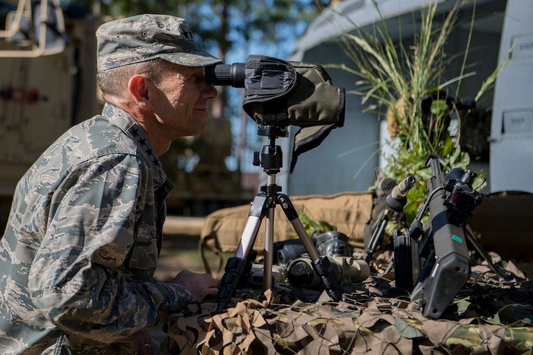 Gen. Mike Holmes, commander of Air Combat Command, looks through a spotter's scope during a capabilities demonstration by the 820th Base Defense Group, Oct. 18, 2017, at Moody Air Force Base, Ga.