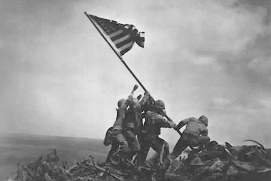 Service members raise the American Flag on Mount Suribachi, Japan.