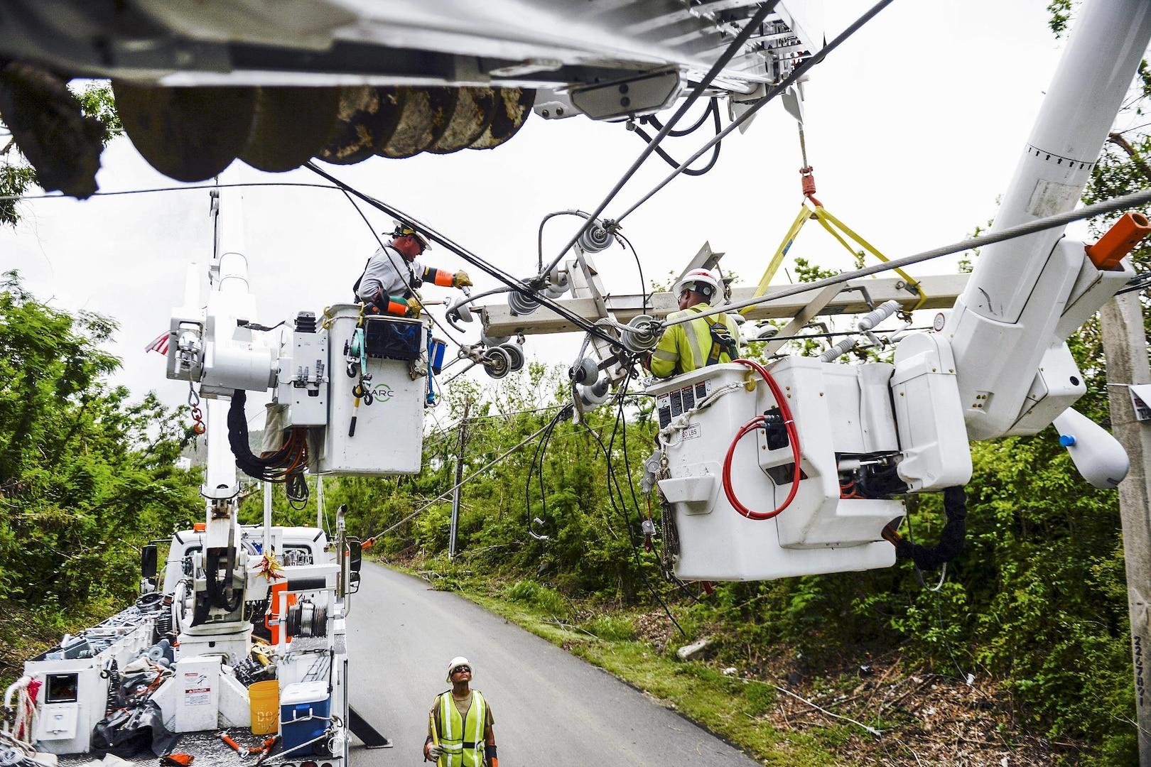 Teams using equipment work to repair power lines in Puerto Rico.