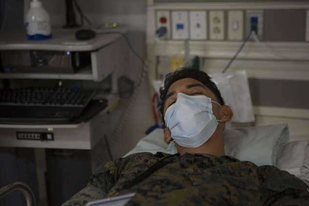 CAMP FOSTER, OKINAWA, Japan— Lance Cpl. Pabel Solis-Zumarraga role plays a patient Oct. 18 during the pandemic influenza isolation exercise aboard Camp Foster, Okinawa, Japan.