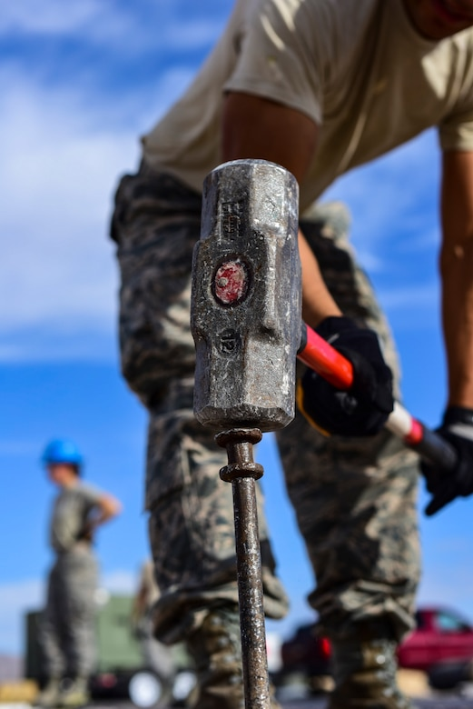 A 99th Civil Engineer Squadron structural engineer drives a stake into the ground during a base emergency engineer force training exercise at Nellis Air Force Base, Nevada, Oct. 19, 2017. The 99th CES conducted their monthly base emergency engineer force training exercise to practice bare base setup and airfield repair. (U.S. Air Force photo by Airman 1st Class Andrew D. Sarver/Released)