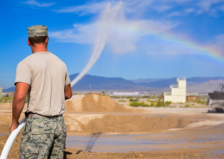 A pavement and construction equipment Airman from the 99th Civil Engineer Squadron sprays water to keep dust from kicking up during a base emergency engineer force training exercise at Nellis Air Force Base, Nevada, Oct. 19, 2017. The exercise was comprised of bare base setup and airfield repair to emphasize pre-deployment training. (U.S. Air Force photo by Airman 1st Class Andrew D. Sarver/Released)