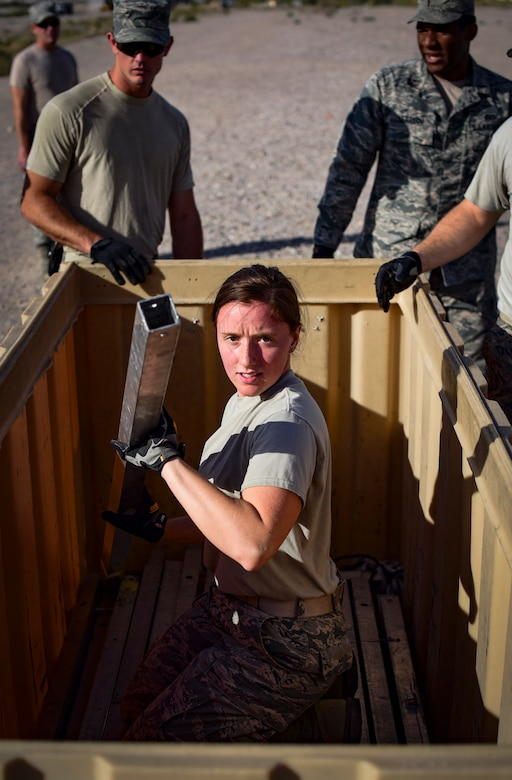 Senior Airman Kelly Martin, 99th Civil Engineer Squadron structural engineer, hands out parts of a field tent during a base emergency engineer force training exercise at Nellis Air Force Base, Nevada, Oct. 19, 2017. 99th CES structural engineers teamed up to build an Alaskan Small Shelter System. The system is commonly used throughout deployed locations. (U.S. Air Force photo by Airman 1st Class Andrew D. Sarver/Released)