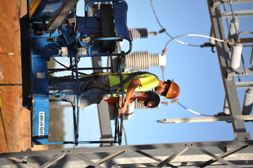 Contractors raise themselves up to work on an electrical substation at Beale Air Force Base