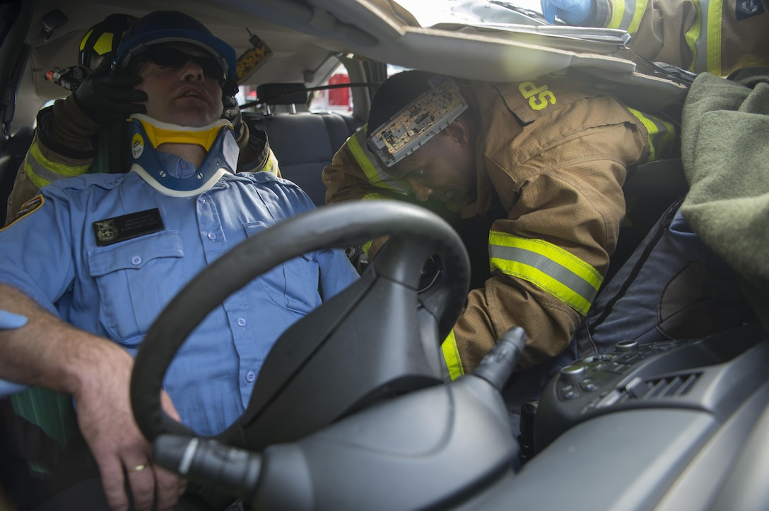 U.S. Air Force Senior Airman Robert Jones, 52nd Civil Engineer Squadron firefighter, extracts Karsten Kurtze, 52nd CES Spangdahlem fire and emergency services, during a simulated vehicle accident on Spangdahlem Air Base, Germany, Oct. 19, 2017. Airmen from the 52nd CES and 52nd Medical Operations Support Squadron train together to practice and execute skills needed for real world scenarios. (U.S. Air Force photo by Senior Airman Dawn M. Weber)