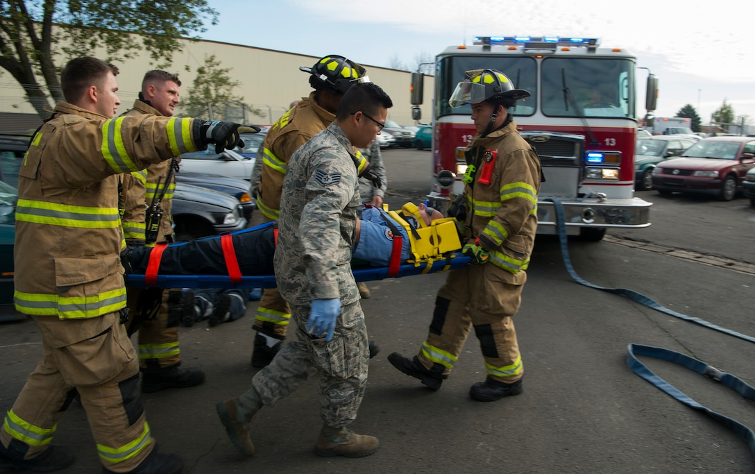 U.S. Air Force Airmen assigned to the 52nd Civil Engineer Squadron and the 52nd Medical Operations Support Squadron carry a patient from a simulated vehicle accident on Spangdahlem Air Base, Germany, Oct. 19, 2017. Airmen from the 52nd CES and 52nd MDOS train together to practice and execute skills needed for real world scenarios. (U.S. Air Force photo by Senior Airman Dawn M. Weber)