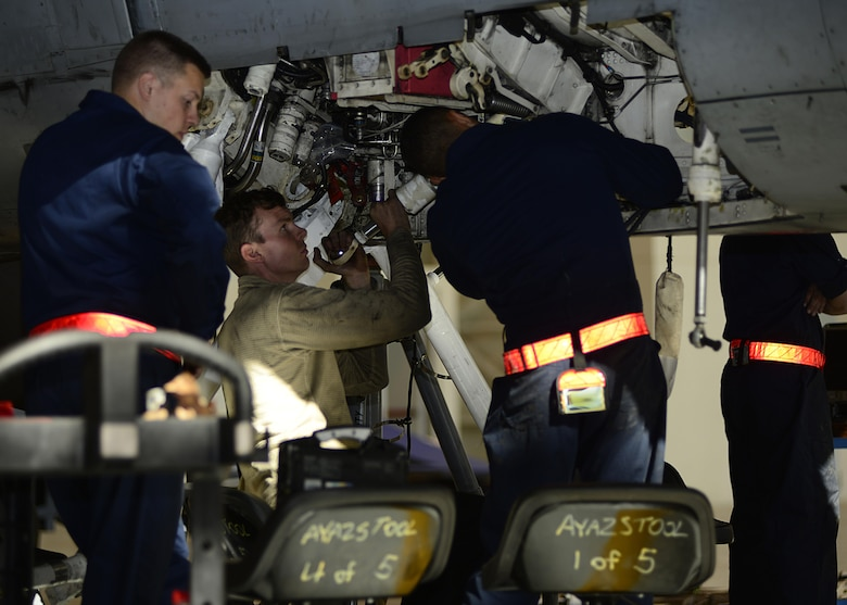 Airmen from the 31st Maintenance Squadron attach a retract actuator to an F-16 Fighting Falcon Oct. 18, 2017, at Aviano Air Base, Italy. A retract actuator pulls the landing gear into the jet. (U.S. Air Force photo by Airman 1st Class Ryan Brooks)