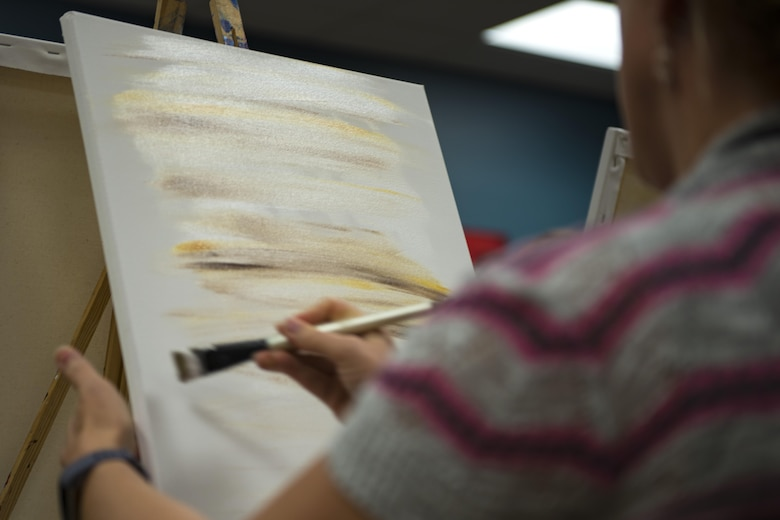 Senior Master Sgt. Anna Keck, 23d Communications Squadron superintendent of operations, paints the background of her painting during a Painting with a Twist Event, Oct. 21, 2017, at Moody Air Force Base, Ga. The event was geared toward providing fun painting experiences for Active Duty members and their dependents, which can help ease some of the stress they face as military families. During the event, participants went through the steps to paint a festive fall pumpkin.  (U.S. Air Force photo by Airman 1st Class Erick Requadt)