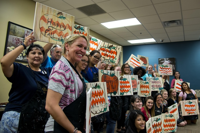 Participants pose with their finished paintings during a Painting with a Twist event, Oct. 21, 2017, at Moody Air Force Base, Ga. At the event, participants went through the steps to paint a festive fall pumpkin. The event was geared toward providing fun painting experiences for Active Duty members and their dependents, which can help ease some of the stress they face as military families. During the event, participants went through the steps to paint a festive fall pumpkin.  (U.S. Air Force photo by Airman 1st Class Erick Requadt)
