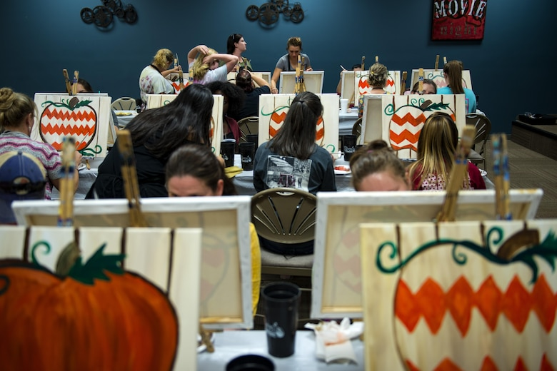 Participants work on their paintings during a Painting with a Twist event, Oct. 21, 2017, at Moody Air Force Base, Ga. At the event, participants went through the steps to paint a festive fall pumpkin.  The event was geared toward providing fun painting experiences for Active Duty members and their dependents, which can help ease some of the stress they face as military families. During the event, participants went through the steps to paint a festive fall pumpkin.  (U.S. Air Force photo by Airman 1st Class Erick Requadt)