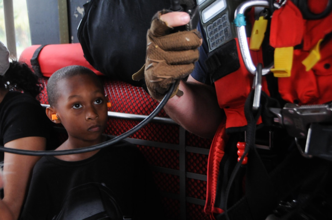 A child looks up at Staff Sgt. Ryan R. Dush, a pararescuemen with the 103rd Rescue Squadron of the 106th Rescue Wing assigned to the New York Air National Guard, while flying in an HH-60 Pave Hawk helicopter over the Houston area, August 30, 2017. The child was safely dropped off to the Montagne Center in Beaumont, Texas. (U.S. Air National Guard photo by Airman 1st Class Daniel H. Farrell)