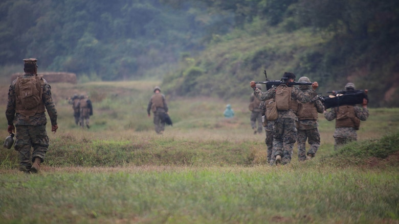 Marines with Marine Air Support Squadron 2, Marine Air Control Group 18, Marine Aircraft Group 36, 1st Marine Aircraft Wing, walk across a field