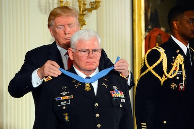President Donald J. Trump places the Medal of Honor around the neck of retired Army Capt. Gary M. Rose.