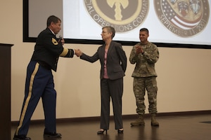 """Dana Bowman (left) presents his personal """"Halo for Freedom"""" coin to DLA Distribution deputy commander Twila Gonzales, Senior Executive Services. Bowman also presents DLA Distribution Susquehanna, Pennsylvania commander, Army Col. Brad Eungard a challenge coin during the DLA Distribution's Multicultural Committee Disability Awareness Month event on Oct. 18."""