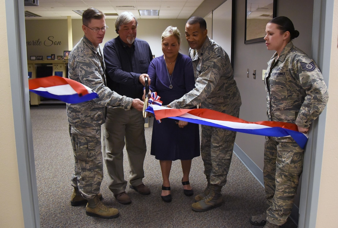 Col. C. Mike Smith, 81st Training Wing vice commander (left), and Lt. Col. Billy Wilson (right), 334th Training Squadron commander, assist Suzi Fernandez and Brent Sibley with cutting a ribbon to a training room during a dedication ceremony to honor their son, Staff Sgt. Forrest Sibley, at Cody Hall Oct. 20, 2017, on Keesler Air Force Base, Mississippi. Sibley was killed in combat in Afghanistan on Aug. 26, 2015. Sibley, a four-time Bronze Star medal recipient, was a combat controller who received his initial technical training from the 334th Training Squadron here. (U.S. Air Force photo by Kemberly Groue)