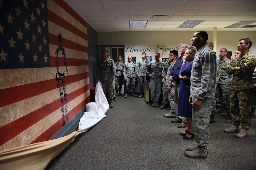 Suzi Fernandez and Brent Sibley are joined by Keesler personnel as they admire a mural inside a training room at Cody Hall during a dedication ceremony to honor their son, Staff Sgt. Forrest Sibley, at Cody Hall Oct. 20, 2017, on Keesler Air Force Base, Mississippi. Sibley was killed in combat in Afghanistan on Aug. 26, 2015. Sibley, a four-time Bronze Star medal recipient, was a combat controller who received his initial technical training from the 334th Training Squadron here. (U.S. Air Force photo by Kemberly Groue)
