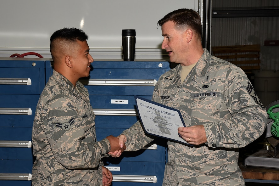 Airman 1st Class Alex Huang, 21st Civil Engineer Squadron electrical power production assistant, receives the first 21st Space Wing Command Chief Airman of the Month at Peterson Air Force Base, Colorado, for October 2017, from Chief Master Sgt. Mark Bronson, 21st SW command chief, for his work performance and merit in the wing. The award will be given monthly to a 21st SW Airman who sets himself apart from his peers. (U.S. Air Force photo by Robb Lingley)