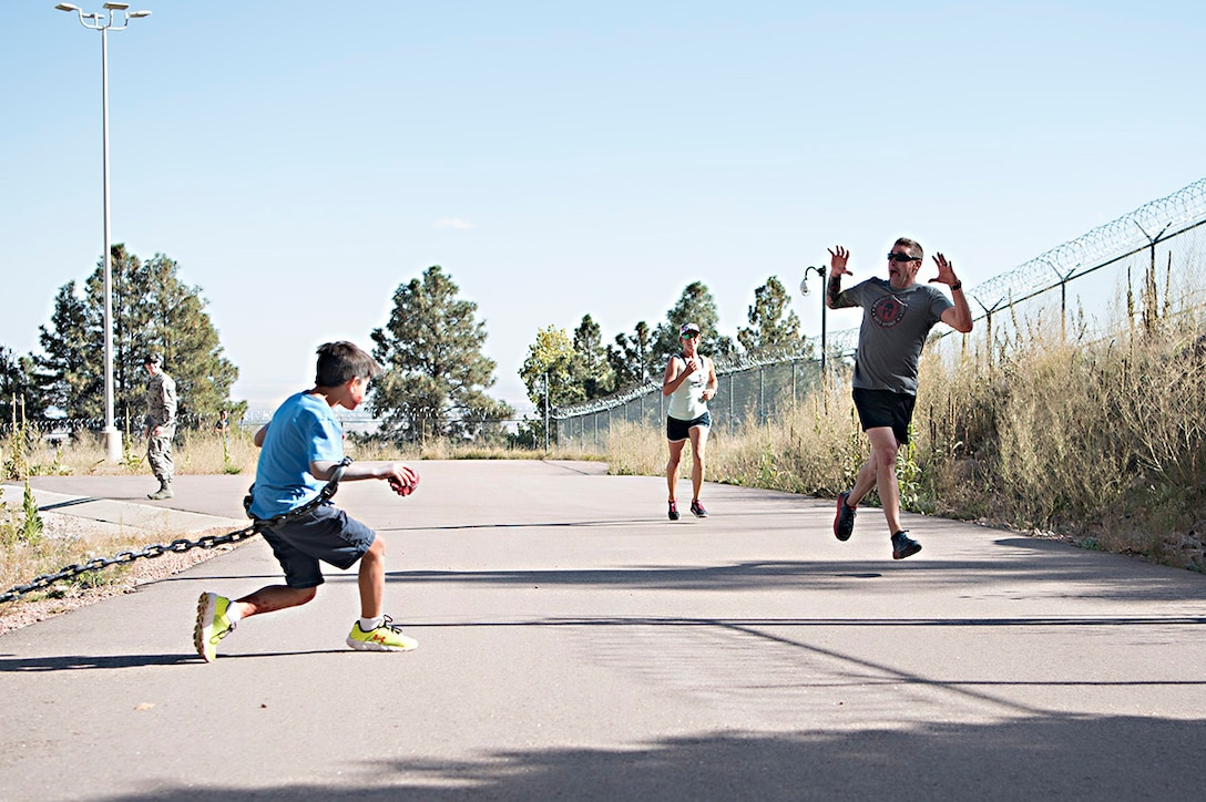 "Kyle Benton (left) gives runners a scare just before they enter the south portal of Cheyenne Mountain Air Force Station, Colorado, during the Zombie Tunnel 5k Fun Run, Oct. 20, 2017. The ""zombies"" were stationed just outside the tunnel in addition to along it's length to provide an eerie atmosphere for the run. (U.S. Air Force photo by Steve Kotecki)"