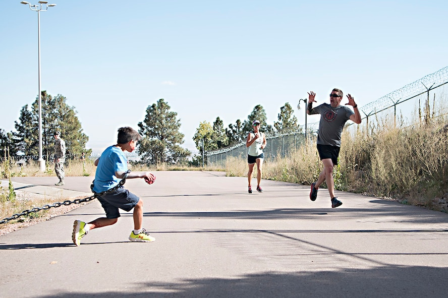 """Kyle Benton (left) gives runners a scare just before they enter the south portal of Cheyenne Mountain Air Force Station, Colorado, during the Zombie Tunnel 5k Fun Run, Oct. 20, 2017. The """"zombies"""" were stationed just outside the tunnel in addition to along it's length to provide an eerie atmosphere for the run. (U.S. Air Force photo by Steve Kotecki)"""