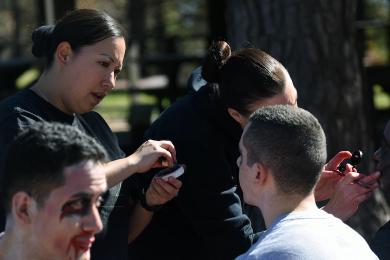 "Tech. Sgt. Kristine Kisamore, 21st Dental Squadron, applies moulage to a participant during the Zombie Tunnel 5k Fun Run at Cheyenne Mountain Air Force Station, Colorado, Oct. 20, 2017. 21st DS volunteers helped ""zombify"" some participants to give runners a fright. (U.S. Air Force photo by Airman 1st Class William Tracy)"
