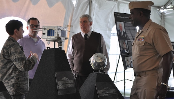 IMAGE: DAHLGREN, Va. (Oct. 16, 2017) – Maj. Erin Dunagan, U.S. Air Force 18th Space Control Squadron, Detachment One commanding officer, briefs civilians and Capt. Godfrey 'Gus' Weekes, Naval Surface Warfare Center Dahlgren Division commanding officer about two satellites on display at the exhibit tent during the centennial kickoff celebration of the Navy base at Dahlgren. The satellite, pictured left, was launched on Aug. 13, 1965 when the space surveillance system was converted to a new operating frequency and it served as a signal source (mHz) for determining if all the surveillance system antenna elements were correctly adjusted in phase. The circular nine-inch diameter satellite was launched on March 9, 1965 as a target for the Navy's space surveillance system. The unusual design of this small satellite permitted it to become a large space target 50 feet in diameter. The Navy transferred operation of the former Naval Space Surveillance System – the nation's oldest sensor built to track satellites and debris in orbit around the Earth – to the Air Force on Oct. 1, 2004. The 18th Space Control Squadron maintains continuous and transparent space situational awareness to assure global freedom of action in space.