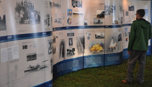 IMAGE: DAHLGREN, Va. (Oct. 16, 2017) – An attended studies the timeline of Dahlgren's history at the exhibit tent during the centennial kickoff celebration of the Navy base at Dahlgren. The ceremony was the first of a series of activities scheduled over the next year to celebrate the significant role Dahlgren has played in bolstering the nation's defense.