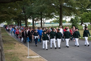 Men and women participate in a half-mile honor walk through Arlington National Cemetery, Va.
