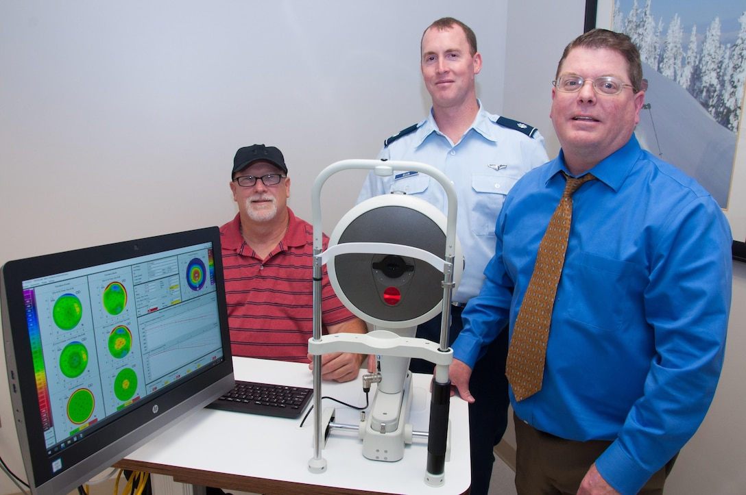 Lt. Col. Jonathan Ellis (center), Ophthalmology Branch manager of the Aeromedical Consultation Service, Dr. Steven Wright (right), optometrist and Scott Humphrey, cornea imaging technician, demonstrate their Pentacam cornea topography device used in pilot screenings and waiver recommendation cases. The device measures the entire cornea with precision, without contact in only a few seconds. (U.S. Air Force photo/John Harrington)